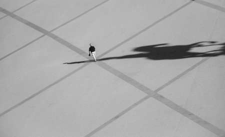 Man walking in the Commerce square (Praca do Comercio) and the shadow of the statue of King Jose I. Photo taken from Rua Augusta Arch fabulous viewpoint, in Lisbon, Portugal