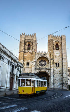 Vintage yellow tram in front of Se Cathedral (Santa Maria Maior de Lisboa), situated on the main road from Baixa to Alfama districts in Lisbon, Portugal 免版税图像