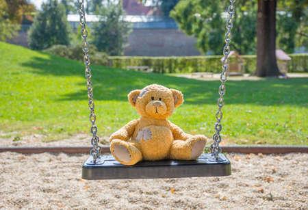 Cute little teddy bear standing alone on a swing in empty park on a beautiful sunny day.