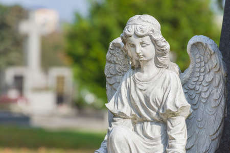 Sculpture of a little angel on a tomb in cemetery. Selective focus Stock fotó