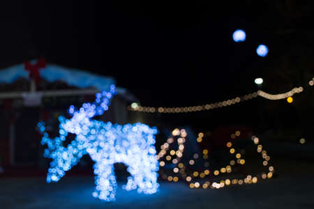 Abstract blurred background with reindeer and Santa's sleigh winter decorations, at night.