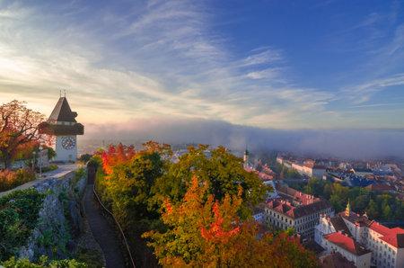 Cityscape of Graz and the famous clock tower (Grazer Uhrturm) on Shlossberg hill, Graz, Styria region, Austria, in autumn, at sunrise