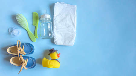 Baby care accessories, newborn baby diaper, pacifier, comb and hair brush, bottle, little boy shoes and toy on a blue background. Wish list or shopping overview for pregnancy, baby shower concept.