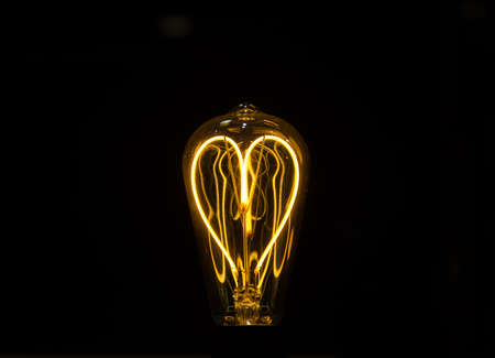 Lightbulb on dark background with bright wire in shape of a heart
