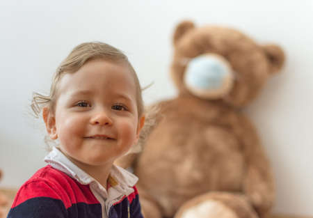 Child playing with his sick teddy bears wearing medical mask against viruses. Role playing, child playing doctor with plush toy. Children and illness concept.
