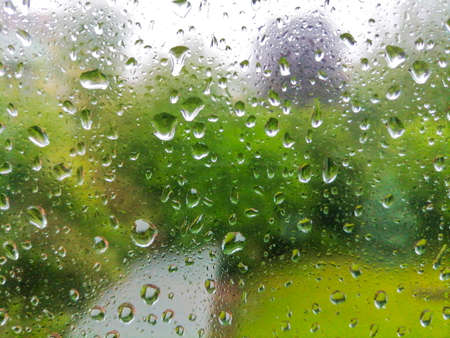 Raindrops on a window in a rainy day, blurry green background