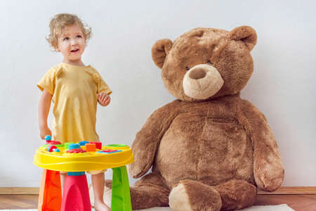 Sweet happy child boy having fun playing at a colorful table of activities with his giant teddy bear, indoor at home