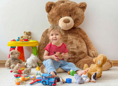 Sweet happy child boy having fun playing with his giant teddy bear and many colorful toys, indoor at home