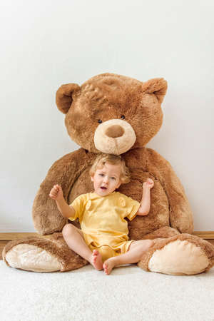 Sweet happy child boy playing with his giant teddy bear, indoor at home