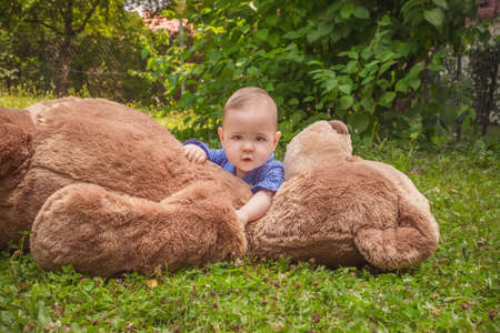 Sweet little baby boy having fun outdoors playing with his giant teddy bear in the park Banque d'images