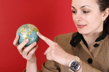Globe in a girl's hands. Isolated on red Stock Photo - 5226865