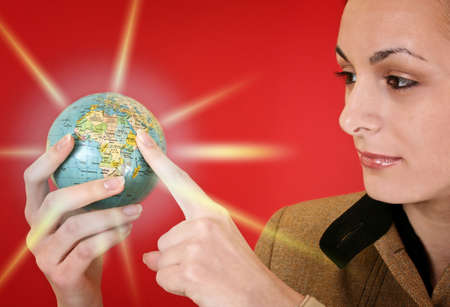 Globe in a girl's hands. Isolated on red Stock Photo - 5250129
