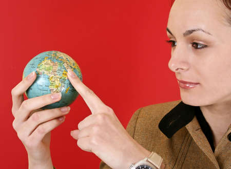 Globe in a girl's hands. Isolated on red Stock Photo - 5577808