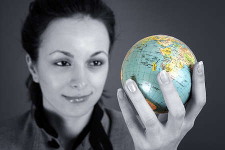 Globe in a girl's hands. Isolated on grey Stock Photo - 5637952