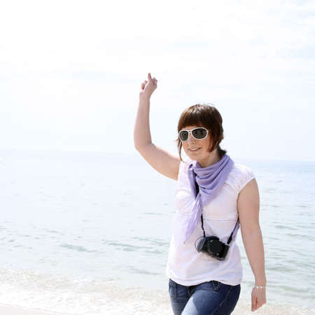 Woman with camera on the beach. photo
