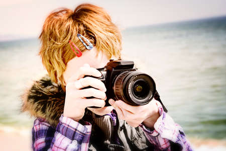Young photographer making pictures on the beach. photo
