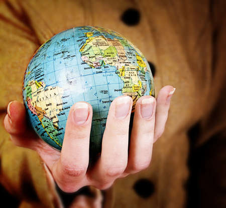 Globe in a girls hands. Macro image Stock Photo