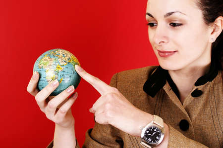 Globe in a girl's hands. Isolated on red Stock Photo - 7653805