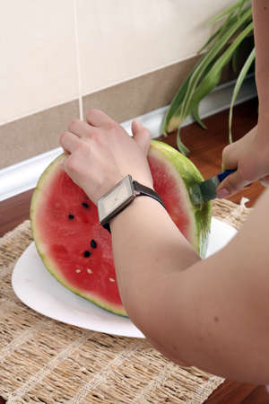 Cutting a slice of juicy water melon photo