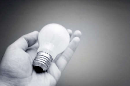 Background with lit lightbulb. Isolated on red photo