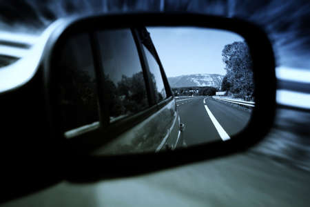 car side: Road seen in a car mirror. Stock Photo