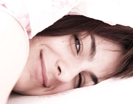 Beautiful young woman sleeping on bed in her bedroom at home in the morning. photo