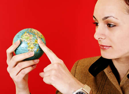 Globe in a girls hands. Isolated on red photo