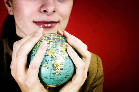 Globe in a girl's hands. Isolated on red Stock Photo - 9594557
