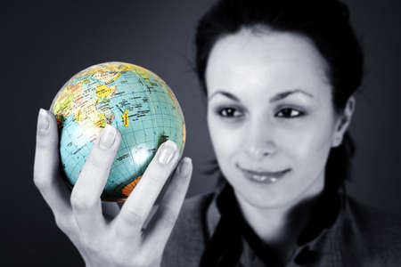 Globe in a girls hands. Isolated on grey photo