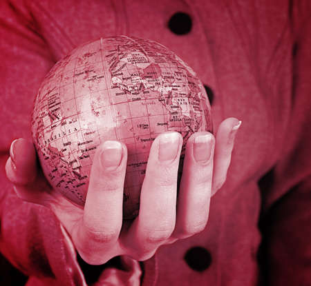 superimpose: Globe in a girls hands. Macro image Stock Photo