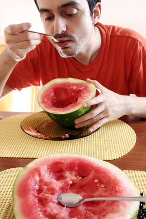 Man eating a slice of watermelon. photo