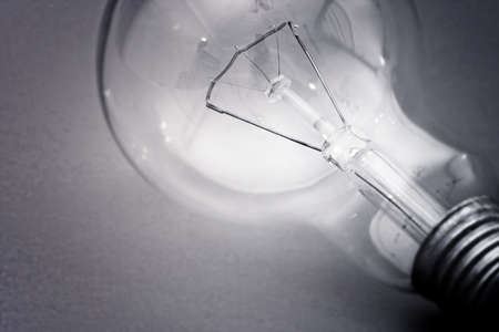 Background with lit lightbulb. Isolated on green photo