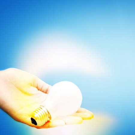 Background with lit lightbulb. Isolated on blue Stock Photo - 16429911
