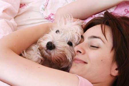 cute westie: Westie sleeping next to woman in bed .