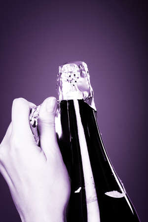 Woman hands opening champagne bottle photo