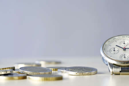 Time and Money - close up photo of one clock and some euro coins photo