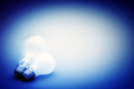 Background with lit lightbulb. Isolated on blue photo