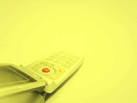 clr: Cell phone isolated on yellow Stock Photo