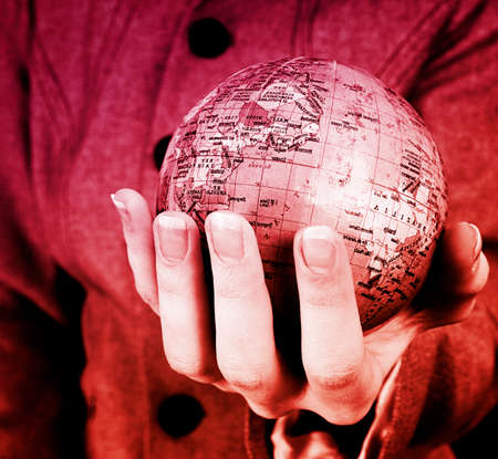 Globe in a girls hands. Macro image Stock Photo