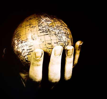 Globe in a girls hands. Macro image isolated on black