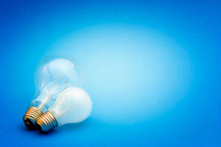 two visions: Background with lit lightbulb. Isolated on blue
