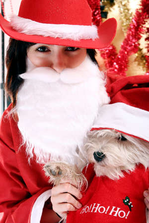 Santa claus with a white puppy in his arms. photo