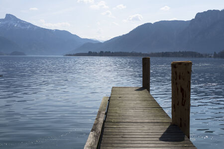 berth: Wooden mooring berth on mondsee lake with mountains in the background Stock Photo
