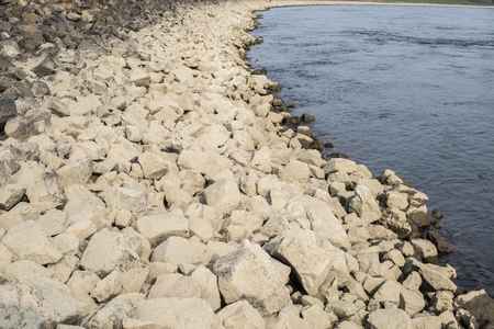 rhein: Stone river bank of Rhein in Germany with big yellow natural stones and rippled water