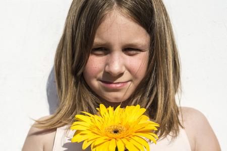 cabello rubio: Muchacha preescolar con el pelo largo y rubio que sostiene la flor brightyellow Foto de archivo