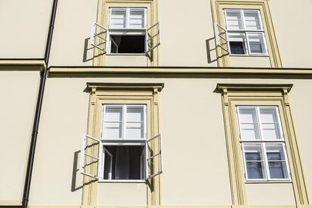 ventanas abiertas: Pared iluminada por el sol del edificio de oficinas de la mañana con las ventanas abiertas de la mitad de las ventanas cubiertas con sombrillas