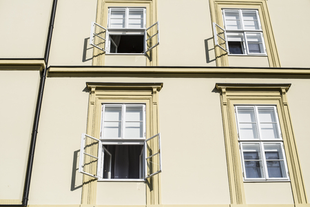 open windows: Sunlit wall of office building in the morning with open windows half of windows covered with sunshades Stock Photo