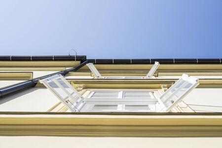 ventanas abiertas: Pared iluminada por el sol del edificio de oficinas de la mañana con las ventanas abiertas