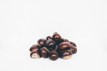 conkers: Pile of glossy horse chestnut seeds on white background retro-styled Stock Photo