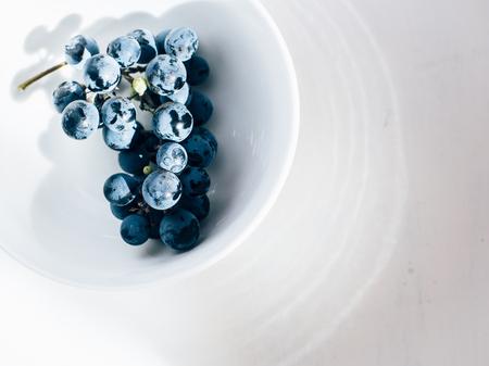 Merlot grape vine in white porcelain bowl on white table Stock Photo